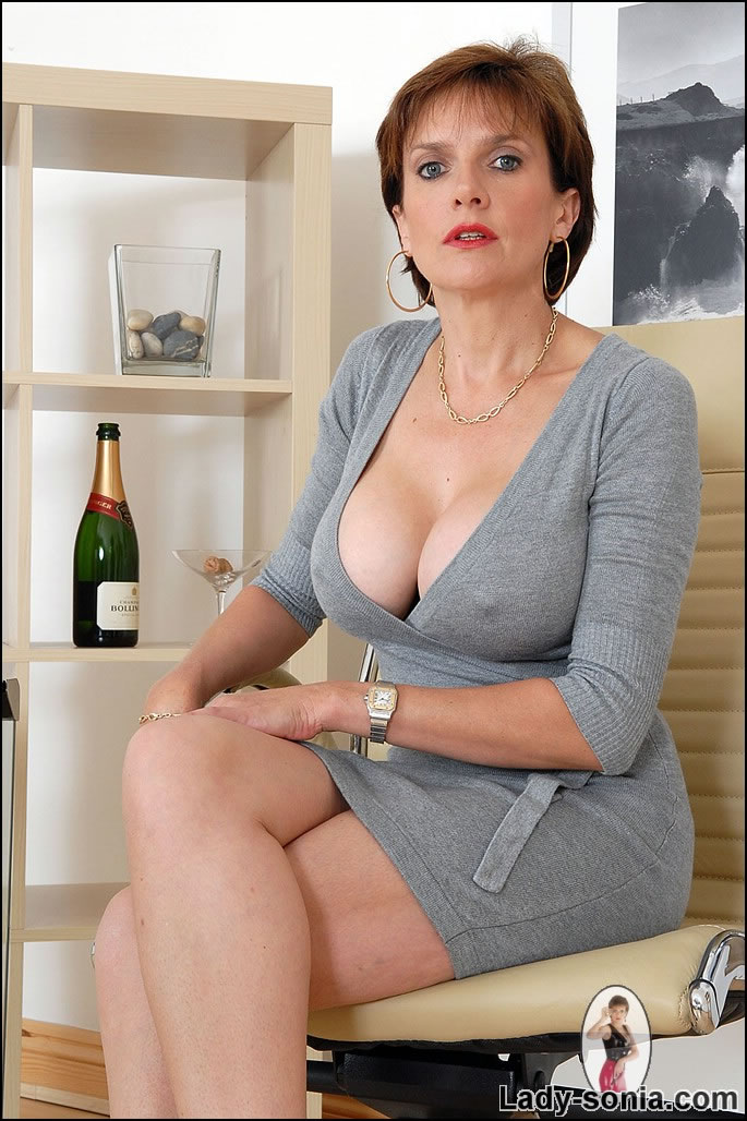 Bossy older lady shows the cleavage between her massive tits and her